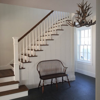 Example of a mid-sized country wooden straight staircase design in Burlington with painted risers