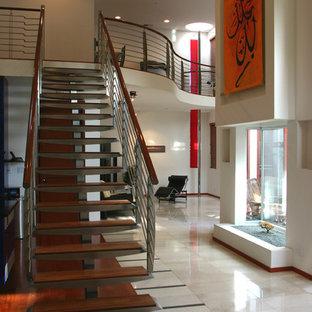 Ejemplo de escalera suspendida, moderna, de tamaño medio, con escalones de metal, contrahuellas de madera y barandilla de metal