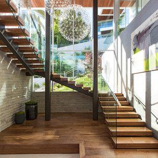 Diseño de escalera en U, actual, extra grande, con escalones de madera, contrahuellas de madera y barandilla de vidrio