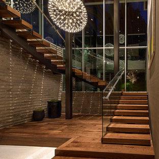 Идея дизайна: огромная п-образная лестница в стиле модернизм с деревянными ступенями и деревянными подступенками