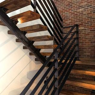 """Esempio di una grande scala a """"U"""" eclettica con pedata in legno, nessuna alzata e parapetto in metallo"""