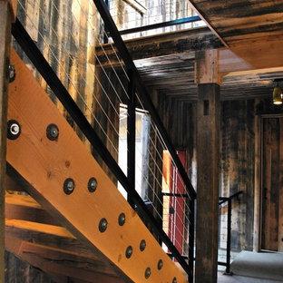 Foto di una scala a rampa dritta country con pedata in legno e nessuna alzata