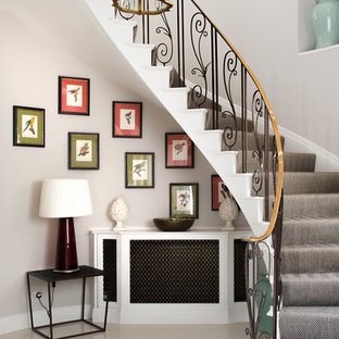 Design ideas for a large classic carpeted curved metal railing staircase in London with carpeted risers.