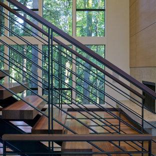 Foto de escalera curva, actual, grande, con escalones de madera, contrahuellas de metal y barandilla de madera