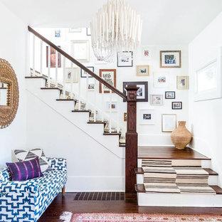 Imagen de escalera en L, ecléctica, de tamaño medio, con escalones de madera, contrahuellas de madera pintada y barandilla de madera