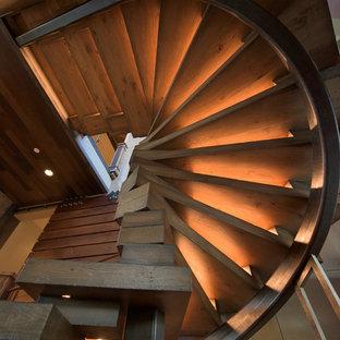 Foto di una grande scala curva industriale con pedata in legno e nessuna alzata