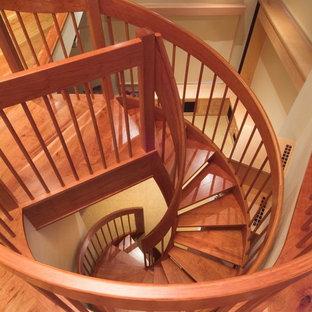 Foto di una scala a chiocciola eclettica di medie dimensioni con pedata in legno e alzata in legno