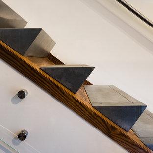 Exemple d'un escalier moderne en L de taille moyenne avec des marches en béton, un garde-corps en verre et des contremarches en bois.