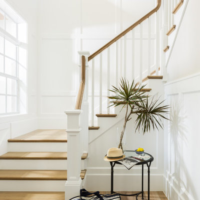 Example of a large beach style wooden l-shaped staircase design in Miami with painted risers