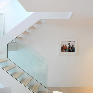 Inspiration for a scandinavian wooden u-shaped staircase remodel in London with glass risers