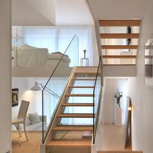 """Ispirazione per una scala a """"U"""" nordica di medie dimensioni con pedata in legno e alzata in vetro"""