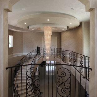 На фото: большая изогнутая лестница в стиле неоклассика (современная классика) с ступенями из плитки и подступенками из плитки
