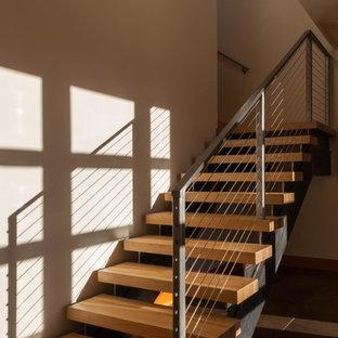 """Foto di una scala a """"L"""" minimal di medie dimensioni con pedata in legno, nessuna alzata e parapetto in cavi"""