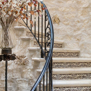 Inspiration för stora medelhavsstil svängda trappor i kalk, med sättsteg i kakel och räcke i metall