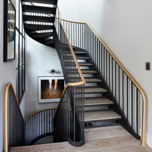 Large traditional wood curved metal railing staircase in London with open risers.