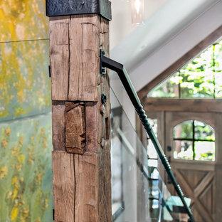 Esempio di una scala a rampa dritta rustica di medie dimensioni con pedata in legno e parapetto in vetro