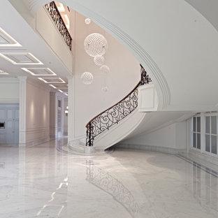 Ispirazione per una grande scala curva chic con pedata in marmo, alzata in pietra calcarea e parapetto in metallo