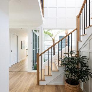 Пример оригинального дизайна: большая п-образная лестница в морском стиле с деревянными ступенями, крашенными деревянными подступенками, перилами из смешанных материалов и панелями на стенах
