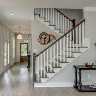 Diseño de escalera en U, de estilo de casa de campo, con escalones de madera y contrahuellas de madera pintada