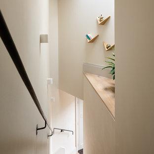 Ejemplo de escalera nórdica con escalones de madera y barandilla de metal