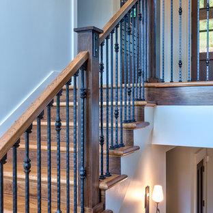 Ejemplo de escalera en U, de estilo americano, de tamaño medio, con escalones de madera, contrahuellas de madera y barandilla de varios materiales