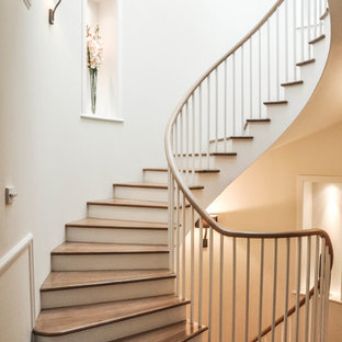 This is an example of a classic wood curved staircase in London with painted wood risers.