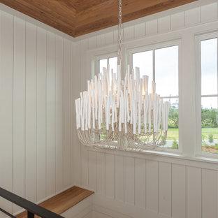 """Immagine di una grande scala a """"U"""" stile marinaro con pedata in legno, alzata in legno verniciato, parapetto in metallo e pareti in perlinato"""