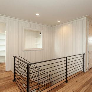 """Idee per una grande scala a """"U"""" stile marino con pedata in legno, alzata in legno verniciato, parapetto in metallo e pareti in perlinato"""