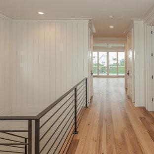 """Esempio di una grande scala a """"U"""" stile marinaro con pedata in legno, alzata in legno verniciato, parapetto in metallo e pareti in perlinato"""