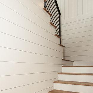 Foto de escalera en U y machihembrado, costera, grande, con escalones de madera, contrahuellas de madera pintada, barandilla de metal y machihembrado
