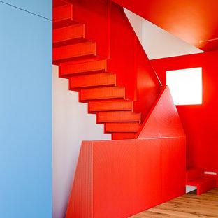 Imagen de escalera en L, minimalista, pequeña, con escalones de metal, contrahuellas de metal y barandilla de metal