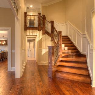Свежая идея для дизайна: огромная изогнутая лестница в стиле ретро с деревянными ступенями и деревянными подступенками - отличное фото интерьера