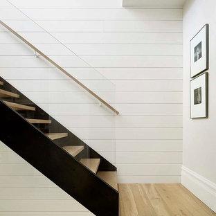 Exemple d'un escalier sans contremarche droit scandinave avec des marches en bois et un garde-corps en verre.