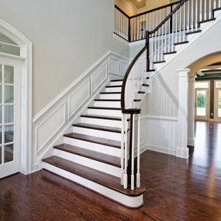 Ejemplo de escalera en L y boiserie, clásica, de tamaño medio, con escalones de madera, barandilla de madera, boiserie y contrahuellas de madera