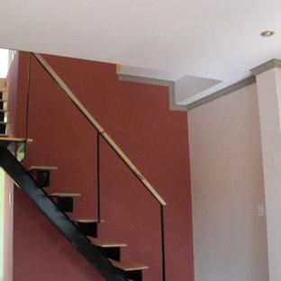 Ejemplo de escalera en L, mediterránea, con escalones de madera y contrahuellas de metal