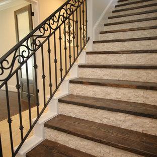 Ejemplo de escalera recta, mediterránea, grande, con escalones de madera, contrahuellas de travertino y barandilla de metal