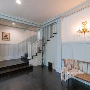 Ejemplo de escalera en U y boiserie, de estilo americano, grande, con escalones de madera, contrahuellas de madera, barandilla de madera y boiserie