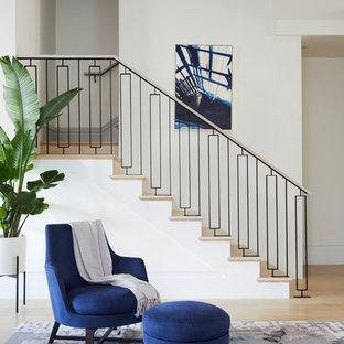 Modelo de escalera clásica renovada con escalones de madera, contrahuellas de madera y barandilla de metal