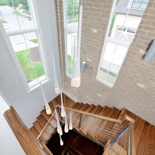Ispirazione per un'ampia scala sospesa minimalista con pedata in legno, nessuna alzata e parapetto in materiali misti