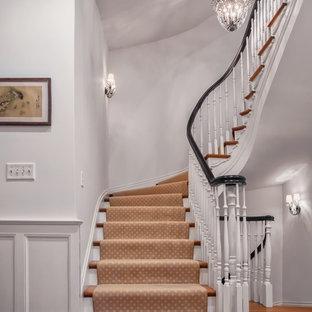 Ispirazione per una grande scala curva chic con pedata in legno e alzata in legno verniciato