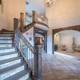 Modelo de escalera curva, de estilo americano, grande, con escalones de madera y contrahuellas con baldosas y/o azulejos