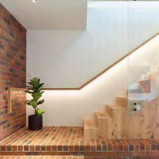 Contemporary wood straight staircase in Brisbane with wood risers and glass railing.