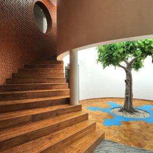 Réalisation d'un très grand escalier courbe ethnique avec des marches en bois, des contremarches en bois et un mur en parement de brique.