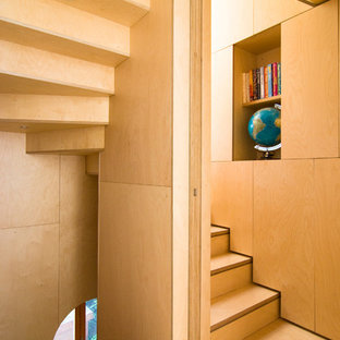 Photo of a small contemporary wood u-shaped staircase in London with wood risers.