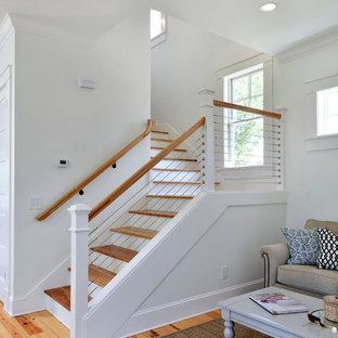 Foto de escalera en L, de estilo de casa de campo, de tamaño medio, con escalones de madera, contrahuellas de madera pintada y barandilla de cable