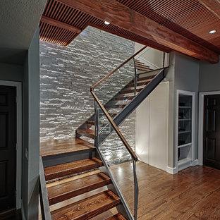 Foto di una grande scala a chiocciola moderna con pedata in legno e nessuna alzata