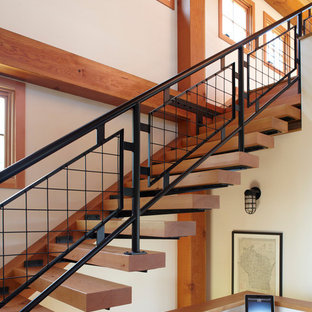 This is an example of a country floating staircase in Milwaukee with open risers and metal railing.