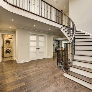 トロントの大きい木のトラディショナルスタイルのおしゃれならせん階段 (フローリングの蹴込み板、混合材の手すり) の写真