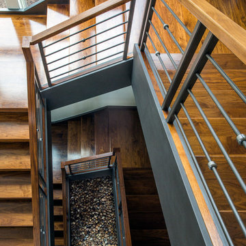 Three Story Floating Walnut Open Tread Staircase with Zen Garden at Base
