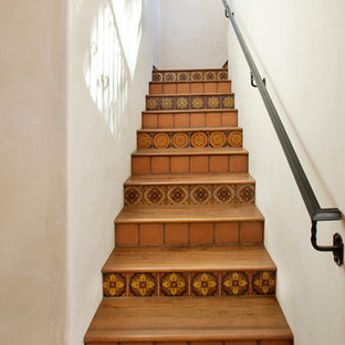 Idee per una scala mediterranea con pedata in legno, parapetto in metallo e alzata in terracotta